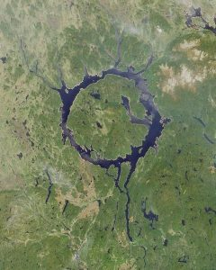 The Manicouagan crater in northern Quebec is an  impact crater so large it can be observed from space. The impact occurred at the end of the Triassic. Image in the public doman, originally from NASA and accessed on Wikipedia.
