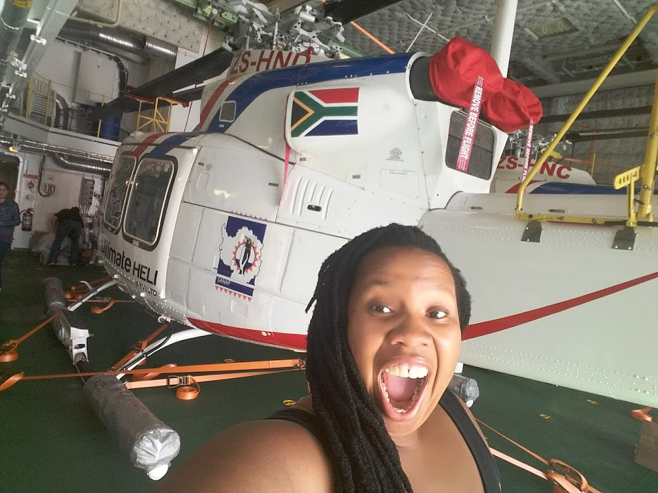Black woman oceanographer standing next to a helicopter