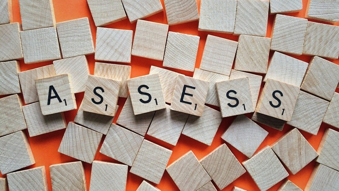 """Scrabble squares spelling out the word """"assess"""""""